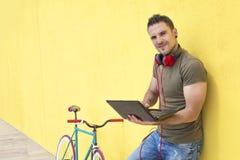 Giovane che lavora con il computer portatile che pende contro una parete gialla Immagine Stock Libera da Diritti