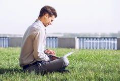 Giovane che lavora con il computer portatile sul prato inglese della città Fotografia Stock Libera da Diritti