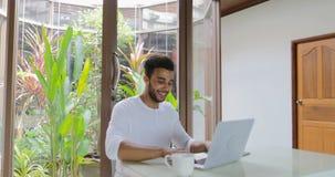 Giovane che lavora con il latino-americano di seduta Guy Typing della Tabella del computer portatile a casa archivi video