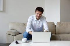 Giovane che lavora dalla casa con il computer portatile Immagini Stock