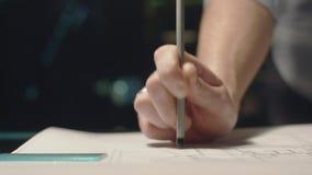 Giovane che lavora nell'ufficio alla notte Tenendo una matita a disposizione Battendo dalla matita sulla tavola archivi video