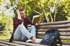 Giovane che legge un libro all'aperto Fotografia Stock