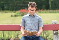 Giovane che legge un libro in parco Fotografia Stock