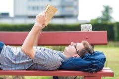 Giovane che legge un libro in parco Fotografie Stock