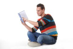 Giovane che legge un libro sul pavimento isolato Fotografia Stock