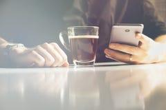 Giovane che mangia il caffè di mattina e che legge le notizie in suo smartphone, tonalità leggera fotografia stock libera da diritti