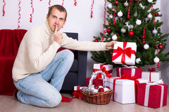 Giovane che mette la scatola del regalo di Natale sotto l'albero di Natale Fotografia Stock