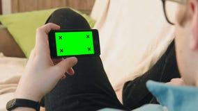 Giovane che mette sul sofà che esamina smartphone con lo schermo verde video d archivio