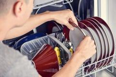 Giovane che mette una macchina lavastoviglie fotografie stock