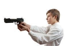 Giovane che mira una pistola nera Fotografia Stock Libera da Diritti