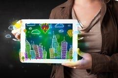 Giovane che mostra compressa con paesaggio urbano disegnato a mano Immagini Stock Libere da Diritti