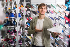 Giovane che mostra le scarpe nel deposito di sport Fotografie Stock Libere da Diritti