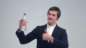 Giovane che mostra una bottiglia di acqua e delle manifestazioni grandi archivi video