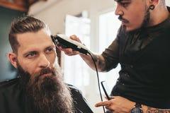 Giovane che ottiene taglio di capelli d'avanguardia al salone immagini stock
