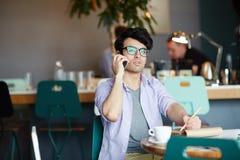 Giovane che parla dal telefono che funziona in caffè Fotografia Stock