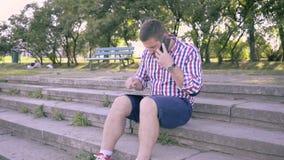 Giovane che parla dallo smartphone e dalla compressa di lettura rapida stock footage
