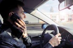 Giovane che parla sul telefono cellulare mentre conducendo un'automobile Fotografia Stock Libera da Diritti