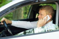 Giovane che parla sul telefono dietro la ruota di un'automobile Immagini Stock Libere da Diritti