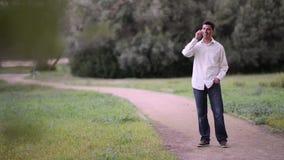 Giovane che parla sul telefono nel parco stock footage