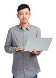 Giovane che per mezzo del computer portatile Immagini Stock