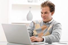 Giovane che per mezzo del computer portatile Fotografia Stock Libera da Diritti
