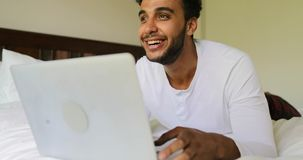 Giovane che per mezzo del computer portatile che si trova sulla mattina sorridente felice di Guy Chatting Online In Bedroom del l stock footage