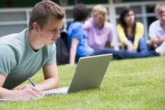 Giovane che per mezzo del computer portatile sul prato inglese della città universitaria Fotografia Stock