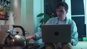 Giovane che per mezzo del computer che si siede alla cucina mentre bollitore che bolle sulla stufa stock footage