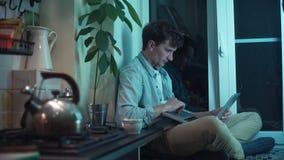 Giovane che per mezzo del computer che si siede alla cucina mentre bollitore che bolle sulla stufa archivi video