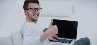 Giovane che per mezzo del suo computer portatile e mostrando pollice su Fine in su Fotografia Stock Libera da Diritti