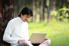 Giovane che per mezzo del suo computer portatile sull'erba Fotografia Stock