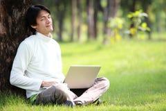 Giovane che per mezzo del suo computer portatile sull'erba Fotografie Stock Libere da Diritti