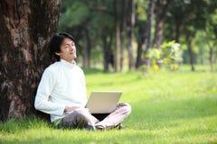 Giovane che per mezzo del suo computer portatile sull'erba Fotografia Stock Libera da Diritti