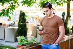 Giovane che per mezzo del telefono mentre stando il giardino vicino del ` s del caffè Immagini Stock Libere da Diritti