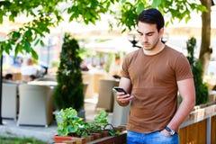 Giovane che per mezzo del telefono mentre stando il giardino vicino del ` s del caffè Immagini Stock