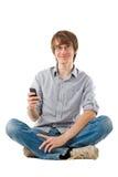 Giovane che per mezzo del telefono mobile per gli sms Fotografie Stock Libere da Diritti