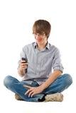 Giovane che per mezzo del telefono mobile per gli sms Fotografia Stock