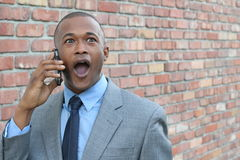Giovane che per mezzo dello Smart Phone che ottiene le notizie scioccanti Uomo d'affari sorpreso che chiama con lo smartphone mob Immagine Stock