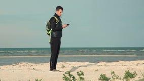 Giovane che per mezzo dello smartphone dal mare per l'orientamento nearsighted video d archivio