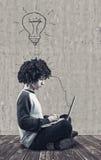 Giovane che per mezzo di un computer portatile Fotografie Stock Libere da Diritti