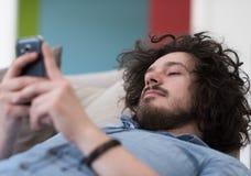 Giovane che per mezzo di un telefono cellulare a casa Immagine Stock Libera da Diritti