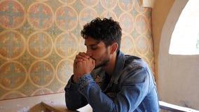 Giovane che prega nella piccola cappella stock footage
