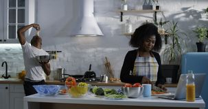 Giovane che prende in giro allegro moglie nella cucina fotografia stock libera da diritti