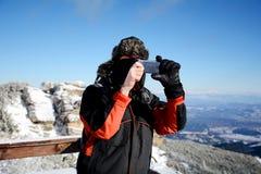 Giovane che prende le immagini con uno smartphone di bella montagna di inverno in Borovets, Bulgaria Fotografie Stock Libere da Diritti