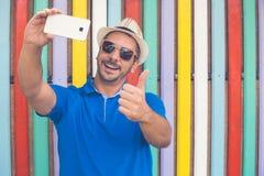 Giovane che prende selfie davanti a fondo variopinto Immagini Stock Libere da Diritti