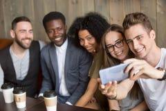 Giovane che prende selfie sullo smartphone alla riunione con gli amici Immagini Stock Libere da Diritti