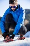 Giovane che prepara camminare sulle racchette da neve sopra il fondo di inverno fotografie stock