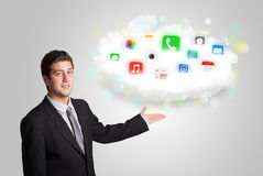Giovane che presenta nuvola con le icone variopinte ed i simboli di app Immagini Stock Libere da Diritti