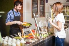Giovane che produce insalata per un cliente immagini stock libere da diritti