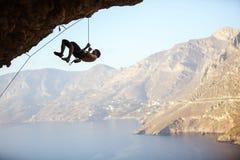 Giovane che prova a raggiungere scogliera per continuare a scalare fotografie stock